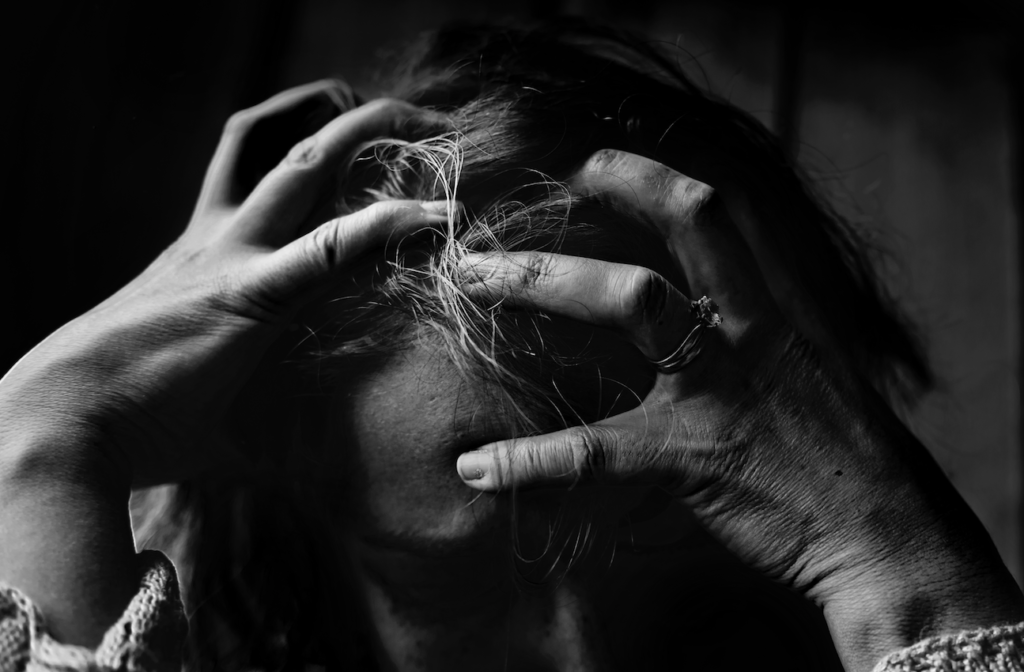 Stressed mom clinches her hair in black and white photo