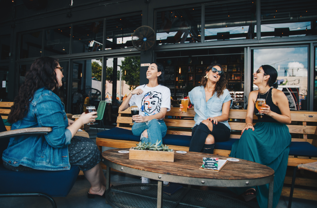 Four stay-at-home moms laugh at happy hour.