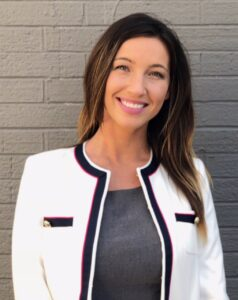 A business woman looks into the camera and smiles in a professional outfit.