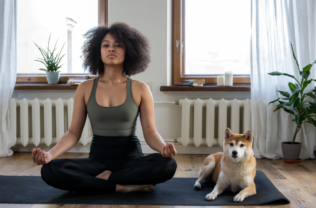 A woman living with chronic illness meditates next to her dog.